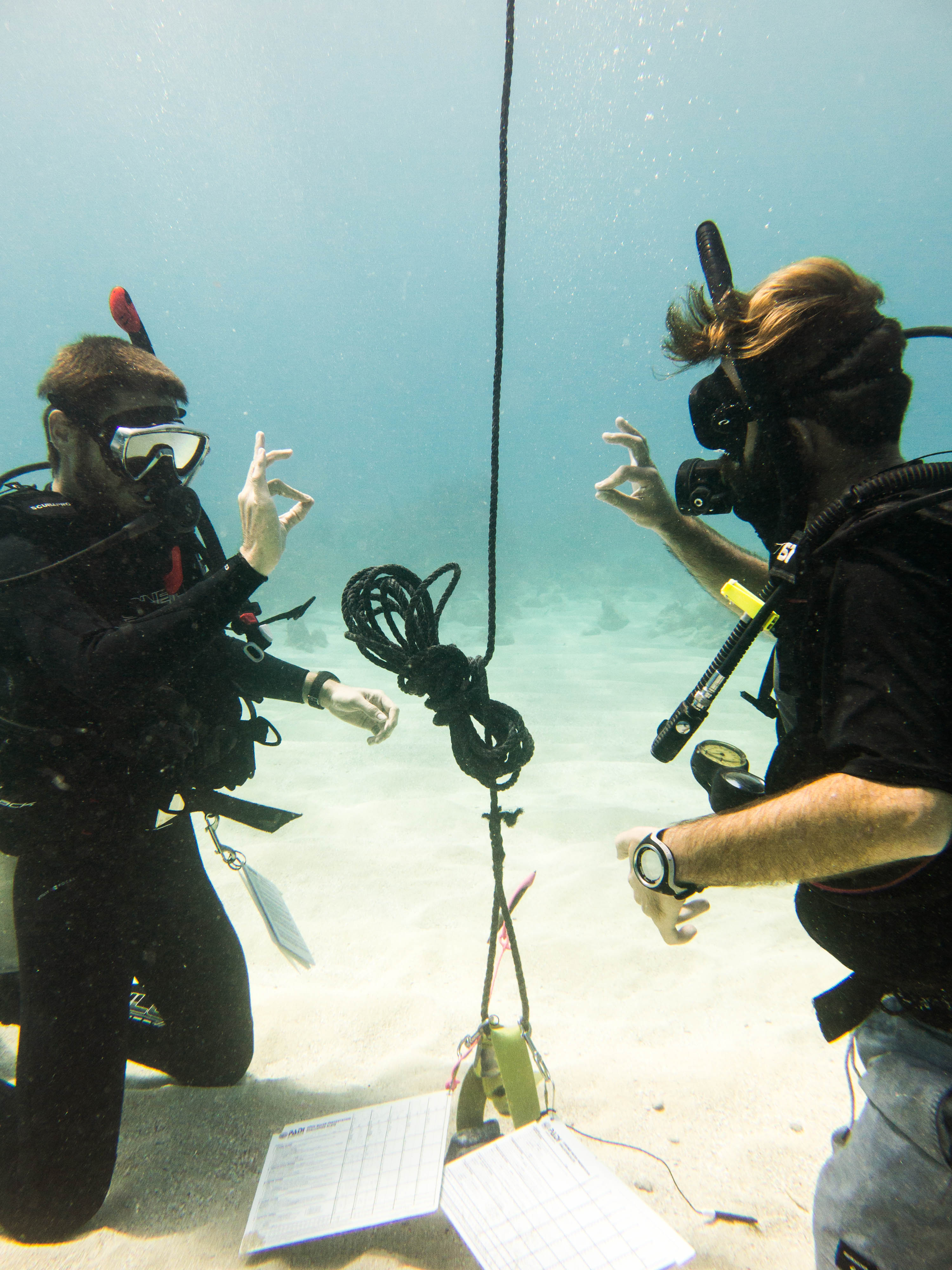 instructor giving the okay signal underwater